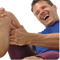 Man wincing after hurting knee playing sports